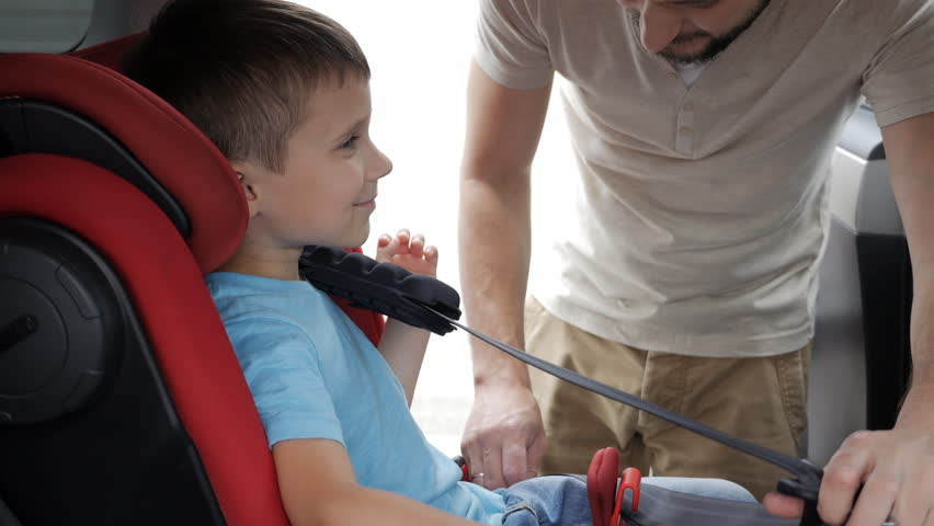Small boy smiling while his father helps to fasten belt on car seat