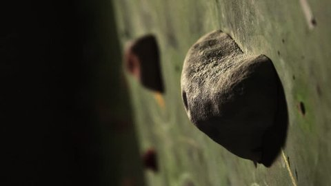 Close-up of a climber climbs on a stone wall indoors. The Sculpture. The hand is fixed at the finish. The exercise is completed.