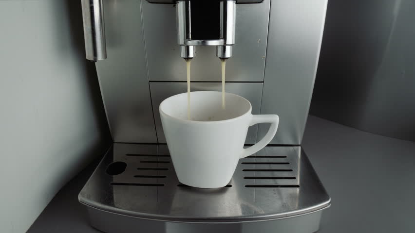 Coffee is poured from the coffee machine and then the male hand takes it. Video footage of working coffee machine at the office.