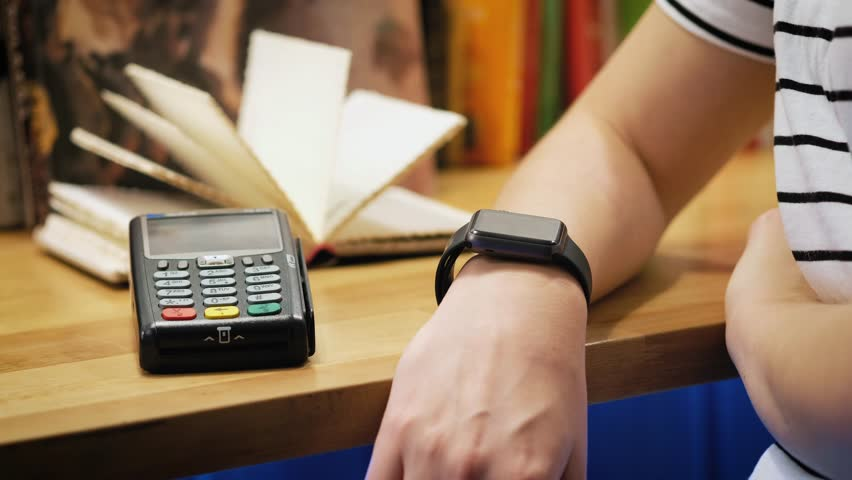 Customer paying with NFC technology by smart watch contactless on terminal in modern cafe. | Shutterstock HD Video #1007172307