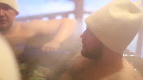 men bathing in outdoor hot tub in winter