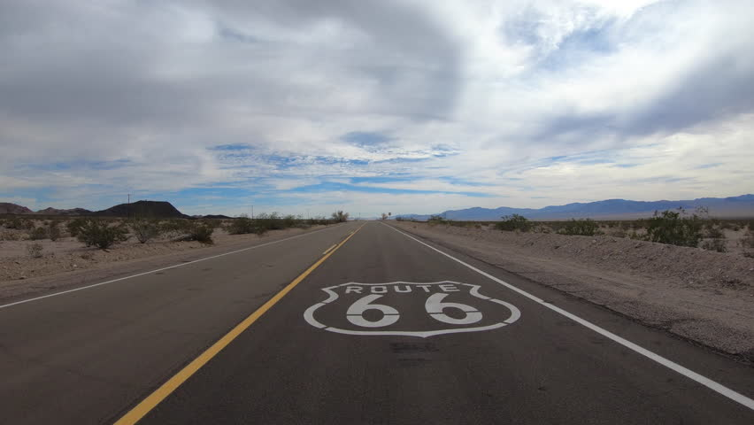 Low aerial fly over of historic Route 66 pavement sign in the scenic California Mojave desert.