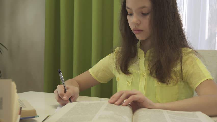Teenager girl does homework at the table stock footage video | Shutterstock HD Video #1007207617