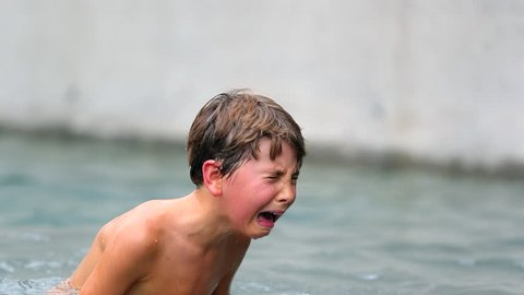 Child in agony after having been physically hurt at the pool. Young boy cries uncontrollably. Child crying in real pain.