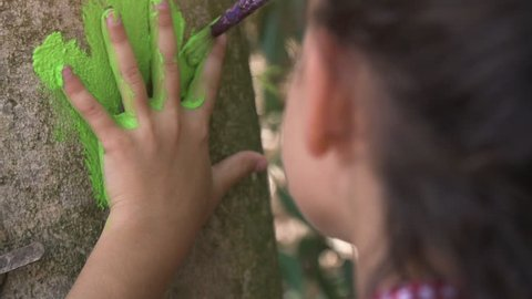 Happy young girl in summer camp leaving handprints with colorful paint on trees art outside kids playing outdoor in park under trees slow motion