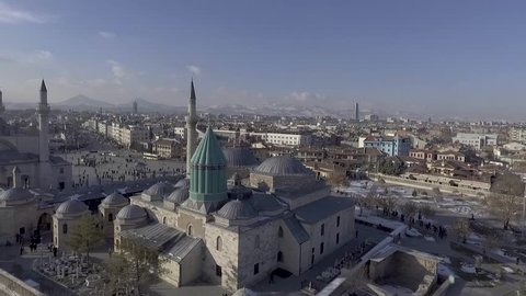 Aerial drone shot over Mevlana Rumi tomb mosque dergah green dome domes city snow cars streets people traffic old town wide shot Karatay, Konya