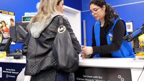 Coquitlam, BC, Canada - February 04, 2018 :  Motion of people returning items at customer service counter inside Walmart store with 4k resolution