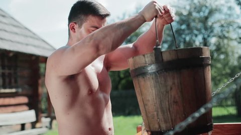 Close up view of sexy shirtless strong barefoot man pulling the full bucket of fresh clear water out of the wooden well. Rural area, village. Long time ago, history, retrospective