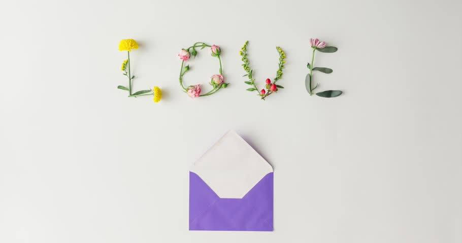 Paper card envelope with flowers forming word love. Flat lay love concept. Stop motion animation.