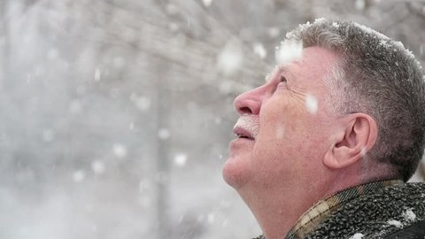 An arty profile of a senior man with white mustashe. He stands in a snowy park in winter. He looks up at falling snowflakes in a picturesque park.
