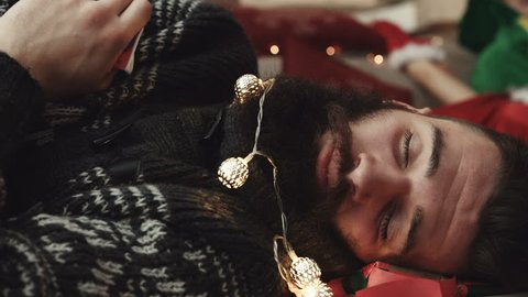 Young attractive guy with garland on beard fast sleeping on floor of beautiful home after cool New Year's Eve party. Close-up.