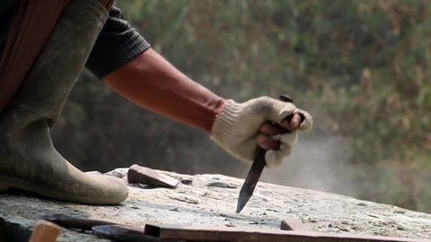 Chopping A Stone With A Chisel And A Hammer