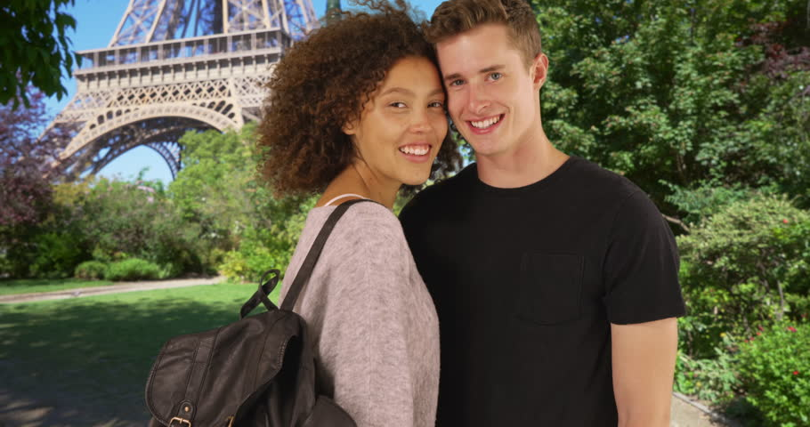 Cheerful couple in Paris smiling and waving at camera. Portrait of millennial male and female tourists standing by the Eiffel Tower. 4k | Shutterstock HD Video #1007326807