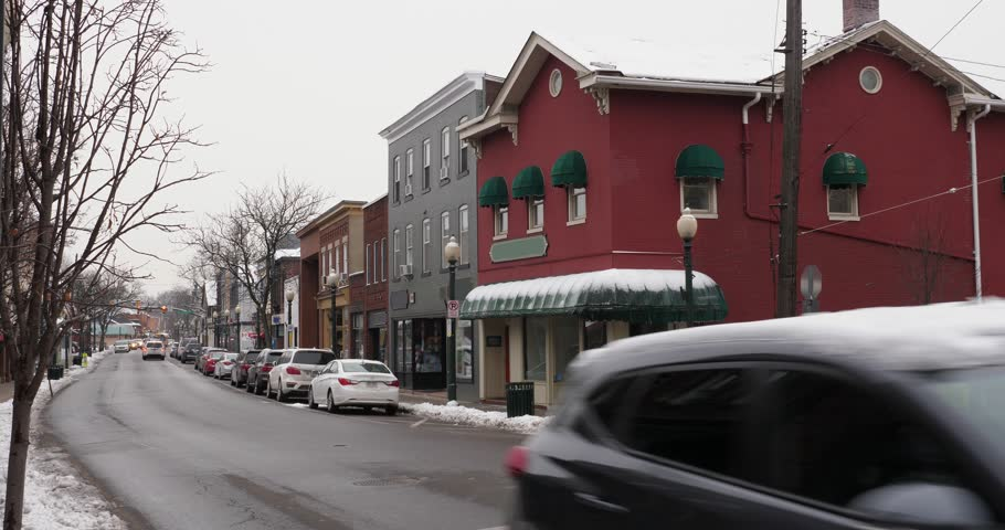 A daytime winter exterior establishing shot of a generic small town's Main Street shopping district storefronts and traffic. Store marquees digitally removed for customization.	 | Shutterstock HD Video #1007346037