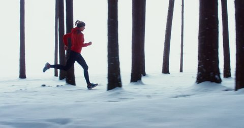 WIDE TRACKING SIDE VIEW Adult fit Caucasian female jogging on winter forest trail. 4K UHD 60 FPS SLO MO