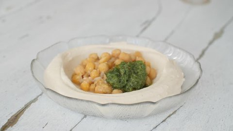 Hummus plate preparation with chickpeas and parsley and paprika and lemon juice.