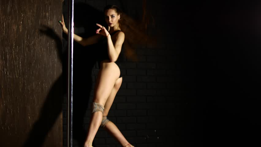 young sexy striptease dancer. sexy tongue out: beautiful young woman  posing. silhouette of pretty stripper woman posing in the studio on a dark  background