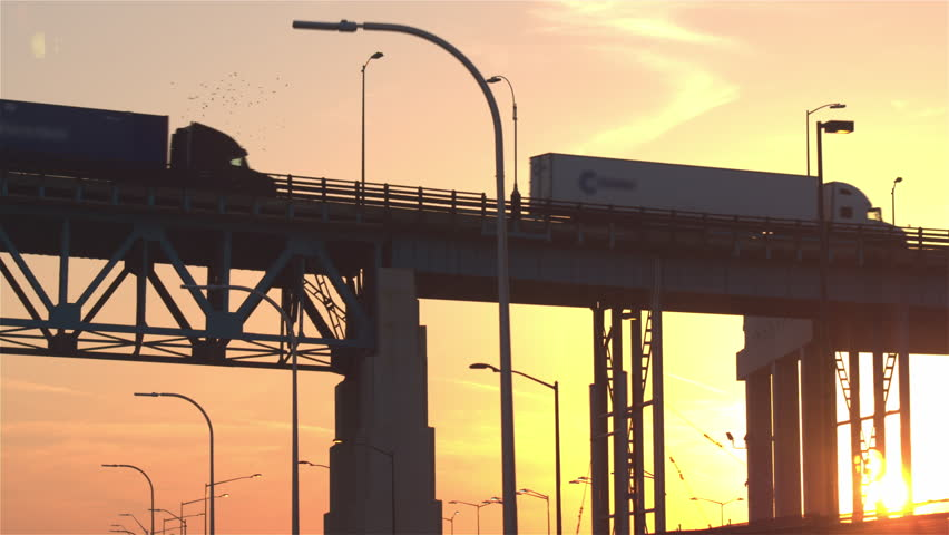 CLOSE UP: Freight container semi trucks driving from the distribution center storage depot over a overpass bridge to the busy multiple lane highway full of cars at beautiful golden light sunset