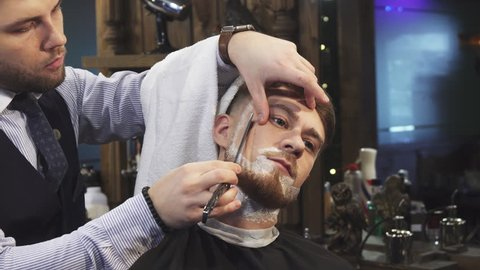 Close up of a handsome young man getting his beard shaved at the barbershop professional barber using a razor shaving his client profession occupation service job barbering styling.