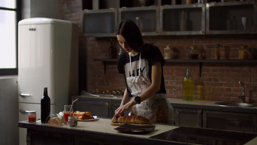 Positive hipster woman in apron putting pieces of fresh baked pie on black square plate in loft style kitchen. Gorgeous young housewife putting slices of tasty pie on plate at home.