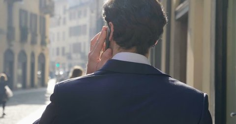 In the city, a businessman answers the phone, send messages and smiles for the beautiful job news. Concept: technology, telephony, business trips, business.