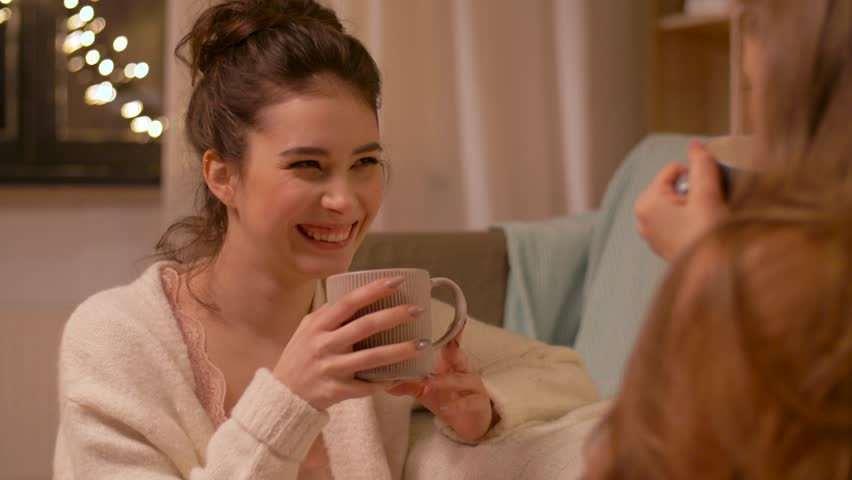 friendship, hygge and pajama party concept - happy young woman or teenage girl drinking tea and talking to friend at home