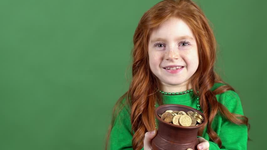Girl red hair celebrating saint patrick's day green wall background looking on pot with gold
