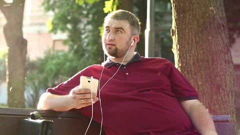 Fat man sits on the bench and listens to music. Businessman sits on the bench in city park and listens to music on his smartphone. Guy with white mobile phone sings a song