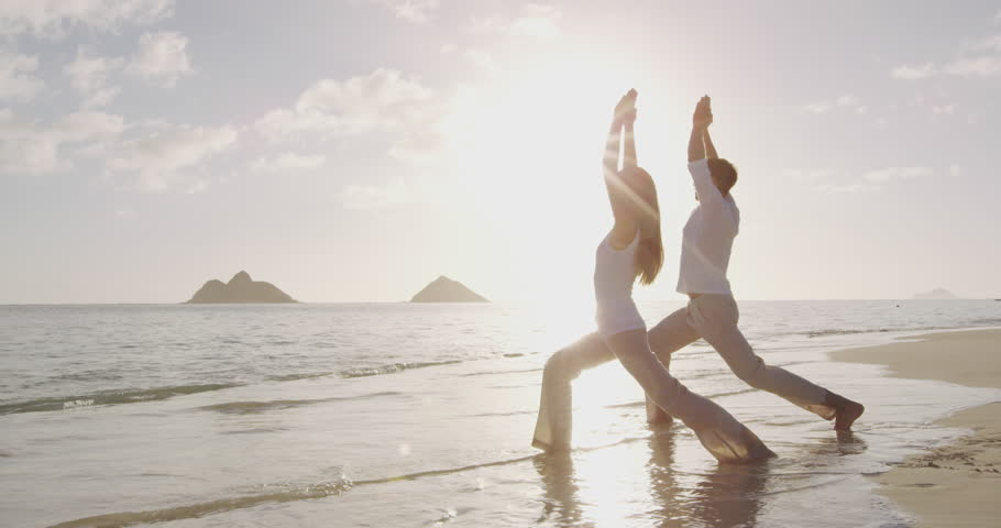 Yoga meditation and wellness lifestyle concept. People, man and woman doing yoga exercises on beach at sunrise on beautiful Warrior 1 pose. tion and yoga meditating on beach.