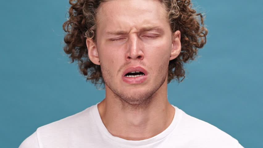 Close up view of tired curly man in t-shirt yawns and covering his mouth over blue background