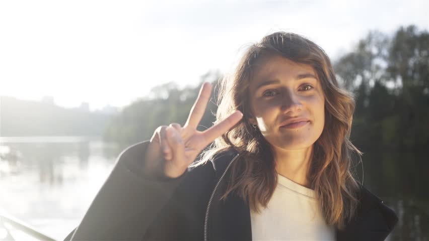 Pretty young brunette in a black hoodie showing a peace sign standing on a river bank on a sunny autumn day. Locked down real time medium shot | Shutterstock HD Video #1007502547