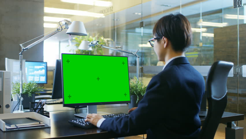 In the Office Businessman works on a Desktop Personal Computer with Mock-up Green Screen. Colleague Enters Office and Takes Place at Her Desk. Shot on RED EPIC-W 8K Helium Cinema Camera. | Shutterstock HD Video #1007506453