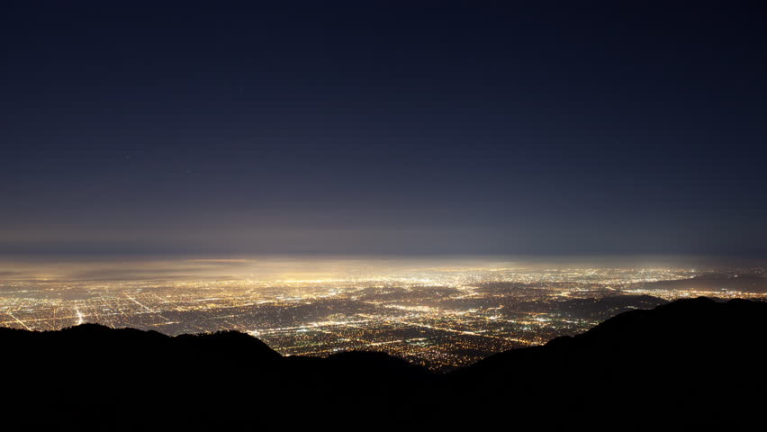 4K time lapse high angle wide shot of stars and airplanes in a clear sky above the glow of the Los Angeles Basin city lights silhouetting the San Gabriel Mountains in California as fog approaches