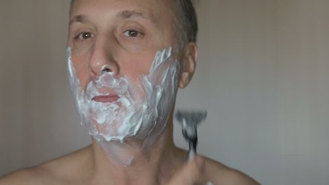 Man shaves his face. Man shaving with foam and manual razer.