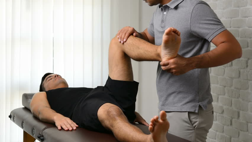 Therapist stretching athlete male patient in clinic - sport physical therapy concept #1007522557