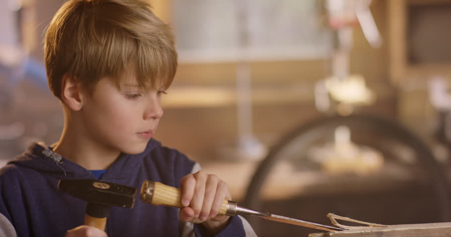Boy is carving some notches into a wooden plank | Shutterstock HD Video #1007537935