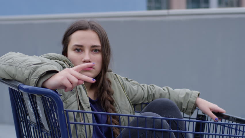 Young Woman Sits In Shopping Cart, Holds Up A Peace Sign With A Very Serious Face, Hilarious And Weird - Shot On Red Scarlet-W Dragon In 4K/ Slow Motion