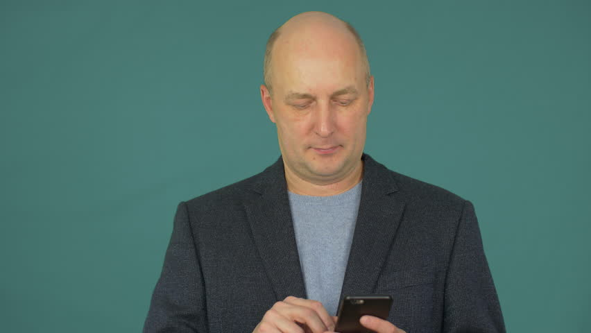 Bald middle aged businessman smiling and talking on smartphone | Shutterstock HD Video #1007557999