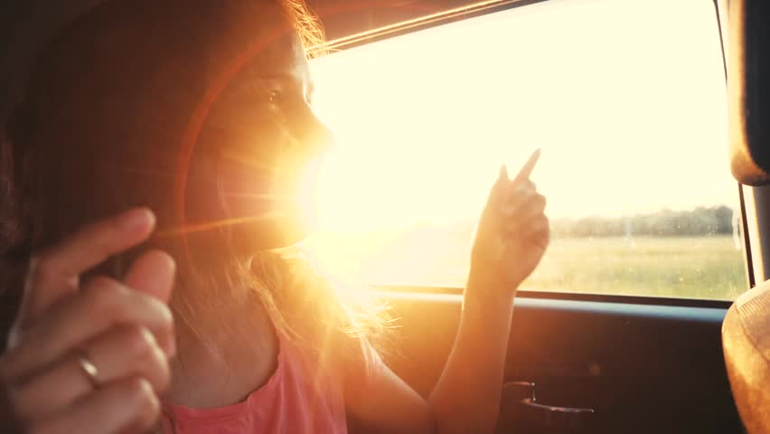 Happy woman smiles, enjoys traveling by car in summertime. Sunset rays. Slow motion sings song and dances. 1920x1080, hd #1007573737