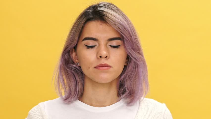 Close up view of Shocked woman in warm cardigan covering her mouth and looking at the camera over yellow background