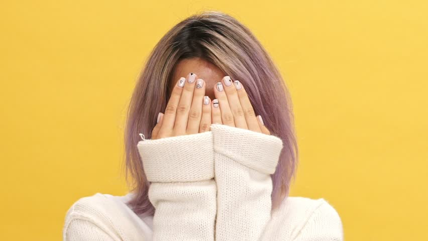 Close up view of cheerful woman in warm cardigan covering and open her face while showing grimaces over yellow background