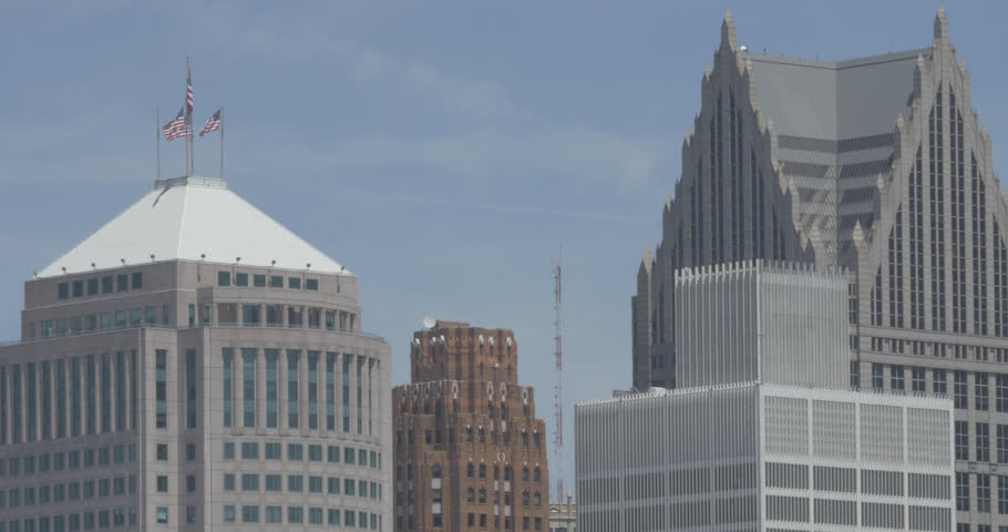 Tight shot of rooftops and american flags in downtown Detroit, Michigan.