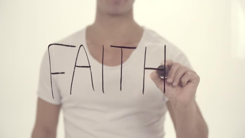 Writing the word FAITH on a glass board