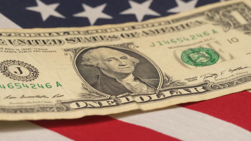 American dollar bill on an United States of America flag on a table. Camera pan   Shutterstock HD Video #1007610427