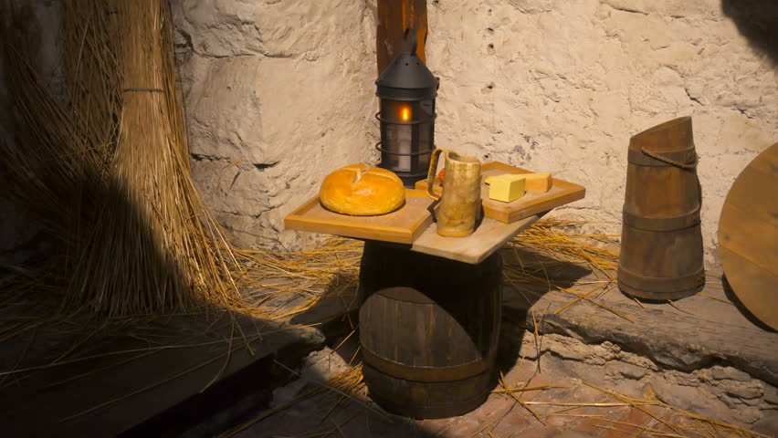 Poor room in a stone house with tools, a candle and food