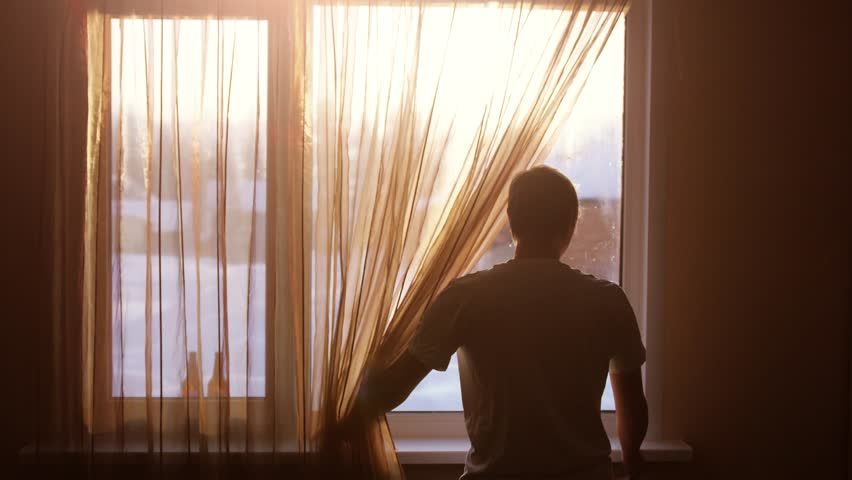 Young male opens curtains to bright sunny winter day and looks out of window in the morning during sunrise. slow motion. 3840x2160