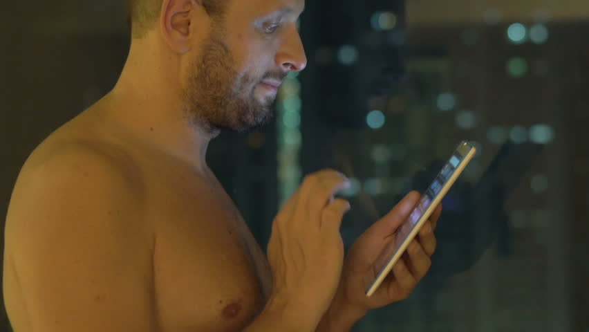 Young, topless man using tablet standing by window at home at night  | Shutterstock HD Video #1007627662