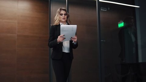 business woman walks down the corridor of an office building and holds documents in her hands. girl in a business suit in office