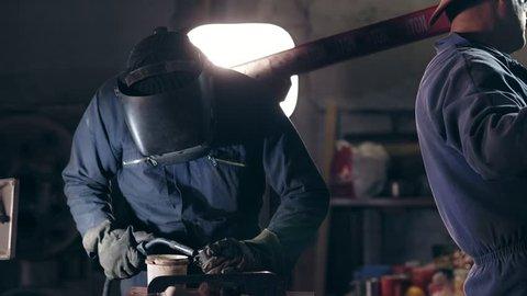 Workers in protective workwear at mechanical hangar. Workman in welding helmet joins two metal pieces together. Dangerous work.