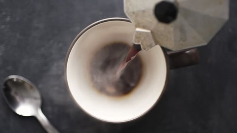 Super slow motion top view of coffee pour into cup from geyser coffee maker